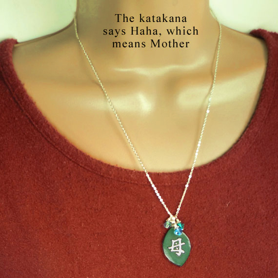 green necklace that says Haha, or Mother in Japanese katakana